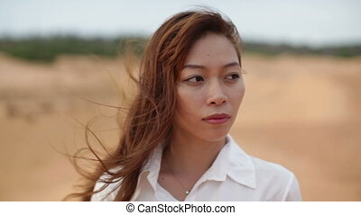 Asian woman serious sad looking outdoor desert wind blowing...