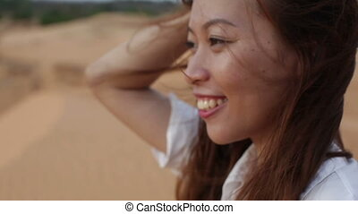 Asian woman smile outdoor desert wind blowing hair, profile...