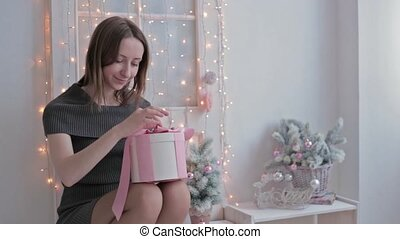Happy young woman opening Christmas present box, HD