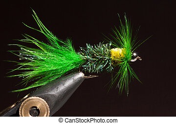 Green wooly bugger trout fly in the wise after being tyed
