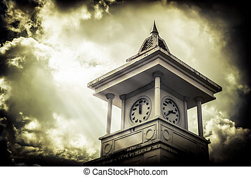 Clock tower with cloudy sky under sunlight on old paper...
