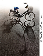 Bike with bright background and shadow on asphalt