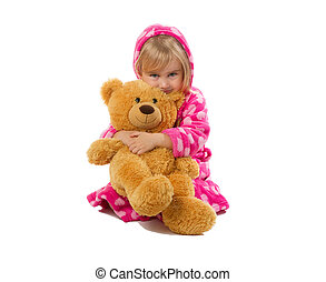 Little girl in warm pink bathrobe with Teddy bear on a white...