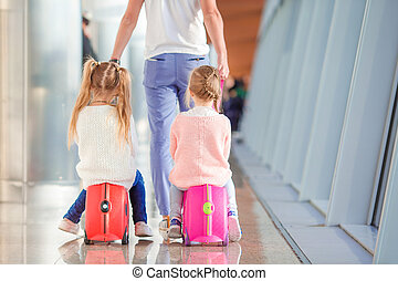Adorable little girls in airport sitting on suitcase waiting...