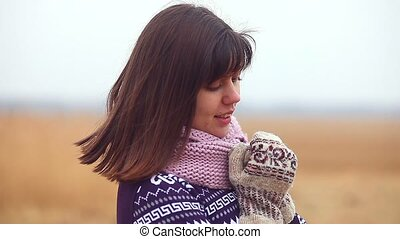 woman girl portrait in sweater scarf and mittens on the...