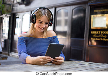 music and e-reader - young woman an ereader and listening to...