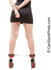 female legs in handcuffed. sex toy. high-heeled shoes