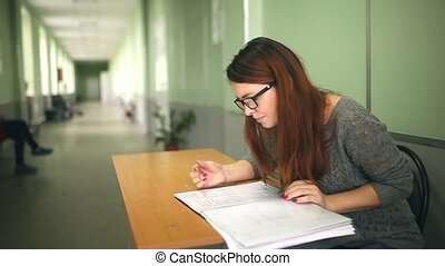 Woman teacher glasses checks homework sitting desk in school...