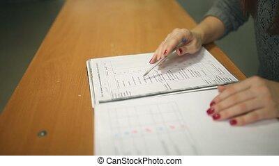 teacher woman glasses checks homework sitting desk in school...
