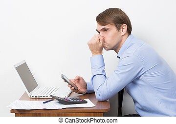 man with a calculator at his desk in the office