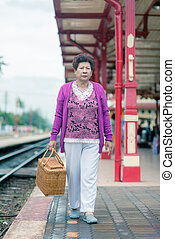 Mature vital elderly woman at the train station. travel on...