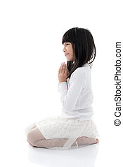 Asian girl praying with clasped hands with blank copy space
