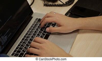 Man is typing computer keyboard - Programming on laptop...