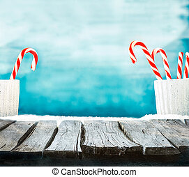 Christmas background. Wooden table with candy cane on snow....