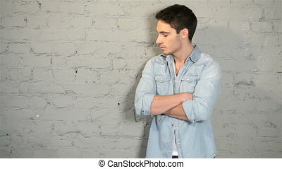 Male posing in a denim and a white T-shirt. A handsome young...