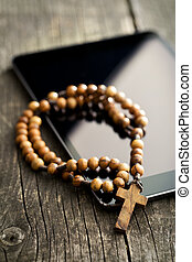 wooden rosary beads with computer tablet on old wooden table
