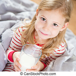 Cute little girl with glass of milk in bedrrom