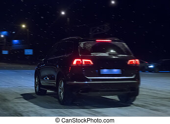 car goes down street at winter night to snowfall