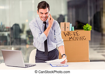 Business moving in office - Young happy businessman with...