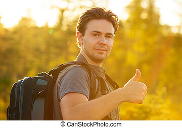 Young man tourist with backpack showing thumbs up handsign...