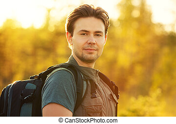 Young man tourist with backpack portrait. Red sunset light.