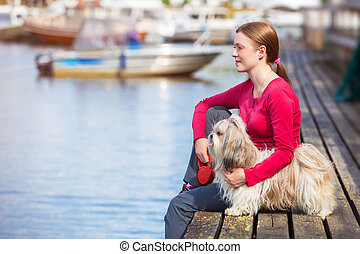 Young woman with shih-tzu dog sitting on town quay with...