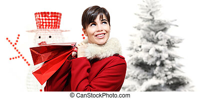 smiling woman with Christmas gift bag, looks up, with trees and snowman in background