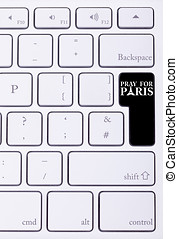 Black button on keyboard with pray for paris sign on it...
