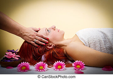 Beautiful young woman receiving facial massage in a spa...