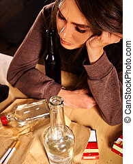 Drunk girl holding bottle of vodka - Drunk girl sitting with...
