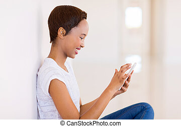 young african girl texting on cell phone