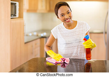 young african woman doing house chores - beautiful young...