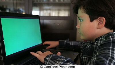 Young boy with green screen laptop monitor