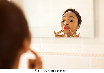 young african woman checking for pimple on her face -...