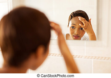 african girl checking her face for pimple looking in the...