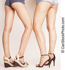 legs of young women, pair butts in jeans shorts isolated on...