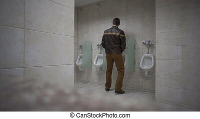 Public Bathroom Man Uses Urinal - Man walks into a public...