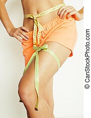 woman measuring waist with tape on knot like a gift, tann...