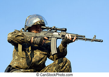 Sniper in camouflage uniform aiming his machine gun