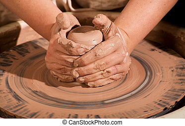 Hands forming clay - hands forming spinning caly wedge on...