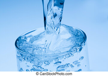 pour water into a glass, symbol photo for drinking water,...