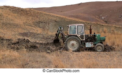 man killed wildlife - tractor dig the hill at day