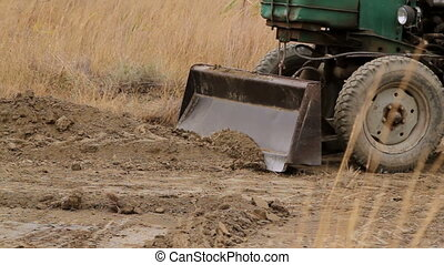 tractor removes the earth - tractor removes the soil heap