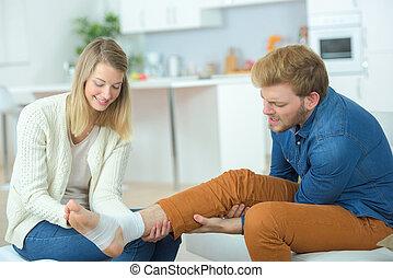 Woman bandaging her boyfriends ankle