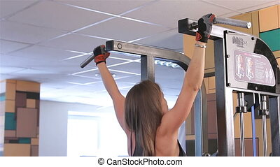 Bodyfitness workout Pull-UPS - Young woman doing exercises...