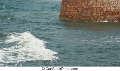 Waves strike the stone wall at sunny day