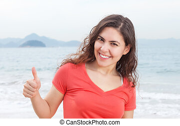 Young woman in a red shirt at beach showing thumb with ocean...