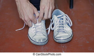 Man Shoes sneakers on his feet. - Young guy laces old white...