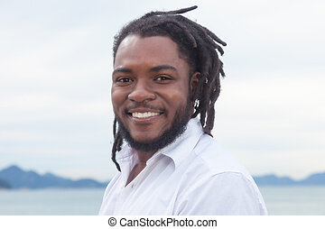 Laughing african american guy with dreadlocks and white...