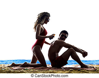 couple applying sun protection on the beach